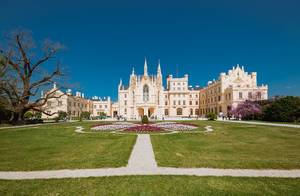 Gesamtansicht von Eisgrub-Schloss in Lednice, Tschechien, mit großem Garten und blauem Himmel