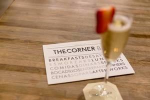 Geschäftskarte des Restaurants & Bar im The Corner Hotel, neben unscharfen Sekt-Drink mit Erdbeerstück, in Barcelona, Spanien