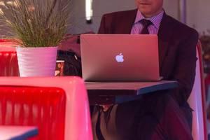 Geschäftsmann mit Anzug und Krawatte am MacBook Laptop