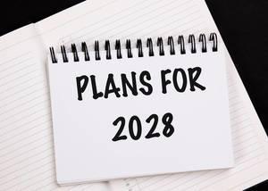 Geschäftsplan für das Jahr 2028, geschrieben auf einem weißen Notizbuch
