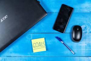 Geschäftsziele-Konzept, mit einem schwarzen Laptop, Smartphone, Maus und Stift auf einem blauen Holztisch