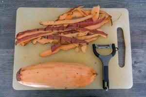 Geschälte Süßkartoffel mit Schäler und Schale auf Schneidebrett