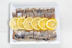 Geschälter, eingelegter Hering in Stücke geschnitten und auf einem weißen Teller serviert mit Zitronenscheiben