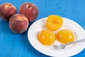Geschälter Pfirsichkompott neben ganzen, reifen Pfirsichen, auf einem blauen Holztisch
