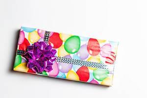 Geschenk in Geburtstags-Geschenkpapier verziert mit einer lila Stern Schleife auf weißem Hintergrund Draufsicht
