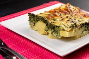 Geschnitten Auflaufstück mit Spinat, Kartoffeln und Käse überbacken auf pinkem Tichset