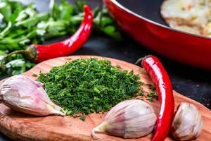 Geschnittene frische Petersilie mit Knoblauchzehen und Paprikapfeffer auf dem Küchenbrett