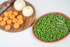 Geschnittene Möhren, Tiefkühl-Erbsen und Zwiebeln auf einem Küchentisch vor dem Kochen