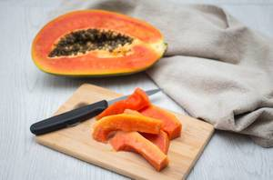 Geschnittene Papaya auf einem Brettchen mit Messer und Papaya-Frucht im Hintergrund