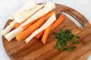 Geschnittene Pastinaken und Karotten, neben Kräutern auf einem Holzbrettchen
