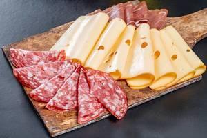 Geschnittene Salami, Käse und Schinken gereiht auf einem alten Holzschneidebrett