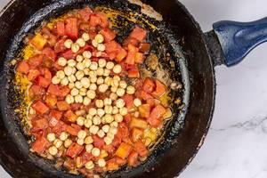 Geschnittene Tomaten mit Kichererbsen in einer Bratpfanne