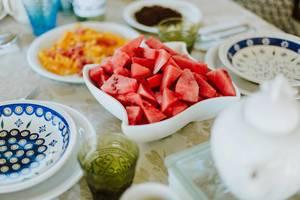Geschnittene Wassermelonen in weißer Schale auf gedecktem Frühstückstisch