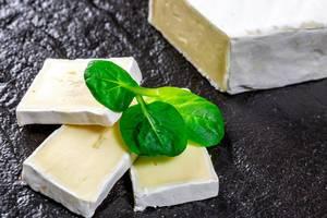 Geschnittener Brie Käse mit Basilikum auf schwarzem Untergrund