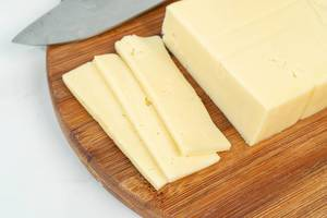 Geschnittener gelber Käse auf einem Holzschneidebrett