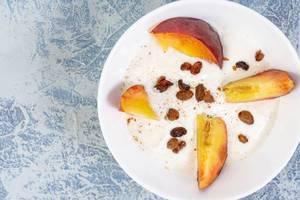 Geschnittener Pfirsich mit Rosinen und Zimt, auf einem weißen Teller