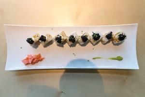 """Geschnittener Sushi """"Lucky No Fish"""", aufgereiht auf einem länglichen Teller, mit veganem Kaviar Topping, veganem Thunfischersatz und Frühlingszwiebeln,"""