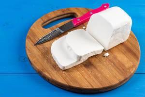 Geschnittener, weißer Käse mit Messer auf einem runden Holzteller, auf einem blauen Holztisch