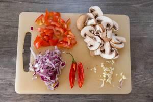 Geschnittenes Gemüse - Tomaten, Pilze, rote Zwiebeln, Chili und Knoblauch auf einem Scheidebrett