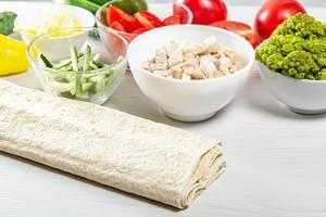 Geschnittenes Gemüse und Hähnchenfleisch in Schalen als Zutaten für davor liegendes Pitabrot