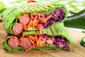 Geschnittenes grünes Pita-Brot gefüllt mit Gemüse und Würstchen auf einem Holzschneidebrett Nahaufnahme