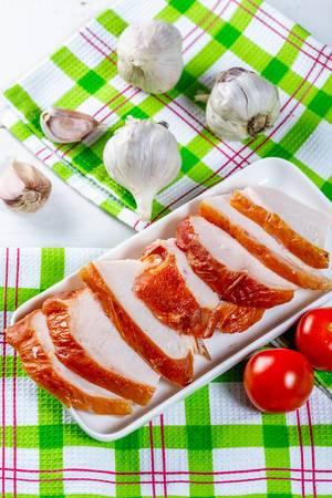 Geschnittenes und geräuchertes Hühnerfilet mit Kirschtomaten und Knoblauch auf grün-weiß-roten Geschirrtüchern