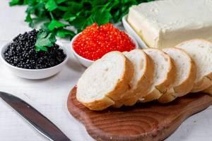 Geschnittenes Weißbrot neben Butter, schwarzem Kaviar und roten Lachskaviar als Delikatesse, auf einem weißen Holztisch