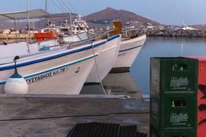 Gestapelte Bierkisten am Hafen, mit Schiffen auf dem Mittelmeer vor der Insel Paros, Griechenland