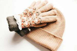Gestrichte Handschuhe und Mütze in beige für kalte Wintertage