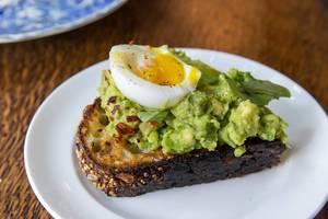 Gesund frühstücken in Chicago mit Ei und Avocado auf Mehrkornbrot-Toast, Nahaufnahme auf einem kleinen weißen Teller