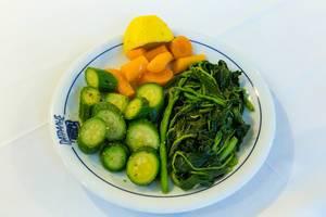 Gesunde Beilage zum Mittagessen, mit Blattspinat, Gurken, Möhren und einer halben Zitrone auf einem weißen Tisch
