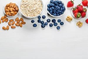 Gesunde Ernährung als Hintergund mit frischen Beeren, Mandeln und Haferflocken