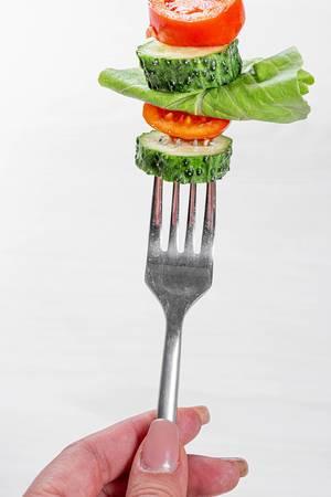 Gesunde Ernährung: Frau hält eine Gabel mit frischem Gemüse