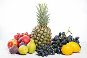 Gesunde Ernährung: Trauben, Äpfel, Birnen, Ananas, Nektarinen, Zitronen und Feigen auf einem Holztisch