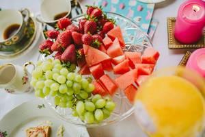 Gesunde Früchte wie Weintrauben, Wassermelone und gereifte Erdbeeren auf einem Glastablett
