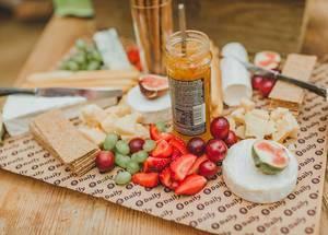 Gesunde Frühstücksplatte mit Käsestücken, Beeren, Weintrauben und Kirschen, auf einem Holztisch