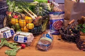Gesunde Lebensmittel auf einem Holztisch: Obst, Gemüse, Studentenfutter, Eier