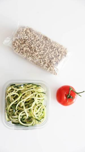"""Gesunde Zucchini-Nudeln """"Zoodles"""" neben einer Tomate und fleischloser, veganer Sonnenblumen-Bolognese, auf weißem Untergrund"""