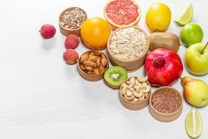 Gesunde Zutaten für ein ausgewogenes Frühstück: Obst, Nüsse und Kerne auf einem weißen Holztisch