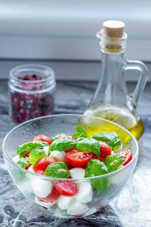 Gesunder Caprese-Salat, mit halben Tomatenstücken, ganzen Basilikum-Blätter, Mozzarella und Olivenöl in einer Karaffe