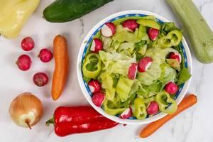 Gesunder grüner Salat mit frischen Radieschen und Paprika umgeben von verschiedenem Gemüse
