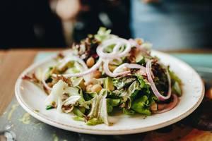 Gesunder Salat mit Kichererbsen, Avocado und Zwiebel. Verschwommener Hintergrund