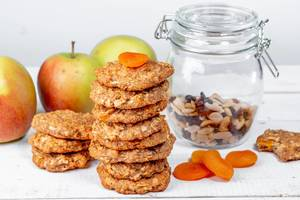 Gesunder Snack aus Haferflocken-Keksen mit einer Nussmischung im Glasgefäß und zuckerfreiem Trockenobst, vor Äpfeln auf einer Küchenzeile