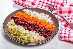 Gesunder vegetarischer Salat aus Kartoffeln, Bohnen, Zwiebeln und Gurken auf einem Holztisch