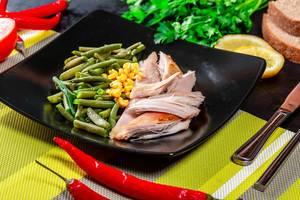Gesundes Essen auf dem Mittagstisch, mit Hähnchenfilet, grünem Spargel und Maiskörnern, auf einem schwarzen Teller