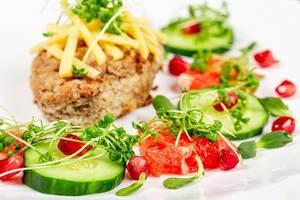 Gesundes Essen mit Kotelett, Käse, Gurkenscheiben, Granatapfelkernen, Pampelmuse und Mikrogrün auf einem weißem Teller Nahaufnahme