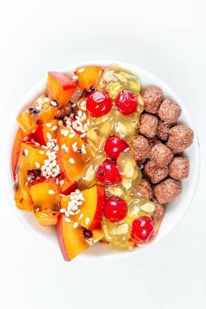 Gesundes Essen mit Maisbällchen, Tamarillo Scheiben, Kiwano Horngurke Fruchtfleisch, Sesam, Rote Johannisbeeren und andere Früchte in einer weißen Schale von oben fotografiert Hochformat