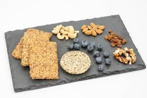 Gesundes Essen und Snacks liegen auf einem Schieferstein, wie Vollkorn-Knäckebrot, Heidelbeeren, Nüsse, Rosinen & Plätzchen mit Chia