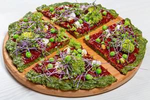 Gesundes Essen: vegetarische Pizza mit Gemüse und Mini-Brokkoli auf einem hölzernen Brett serviert