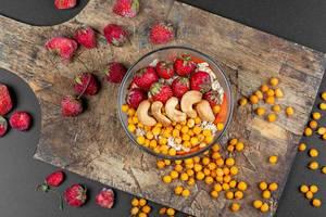 Gesundes Frühstück in einer Glasschale mit Haferflocken, Cashew Nüssen, Erdbeeren und Sanddornbeeren auf einem Holzschneidebrett von oben fotografiert